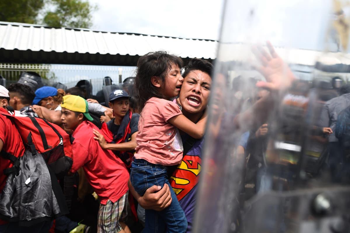 Hondurasilainen siirtolainen lapsi sylissään huutaa meksikolaisille poliiseille yrittäessään ylittää Guatemalan ja Meksikon välistä rajaa.