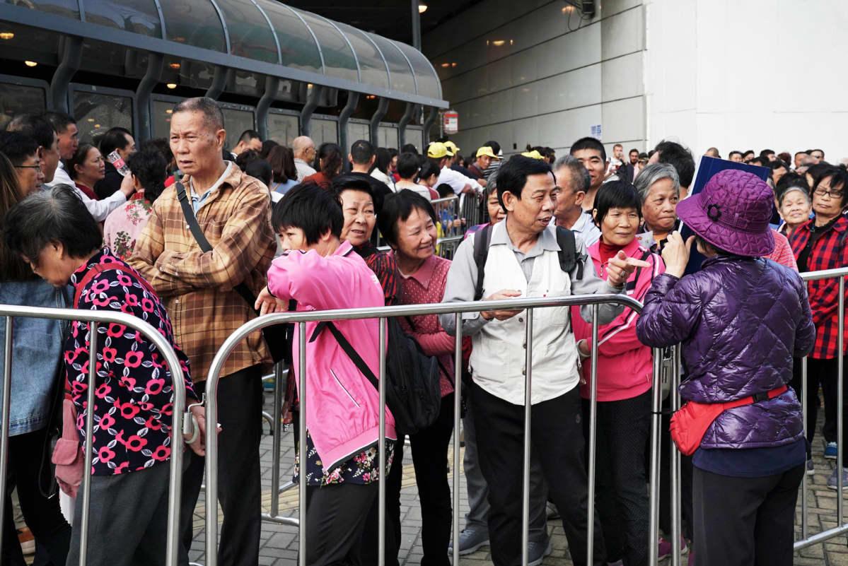 Turistit jonottavat bussiin.