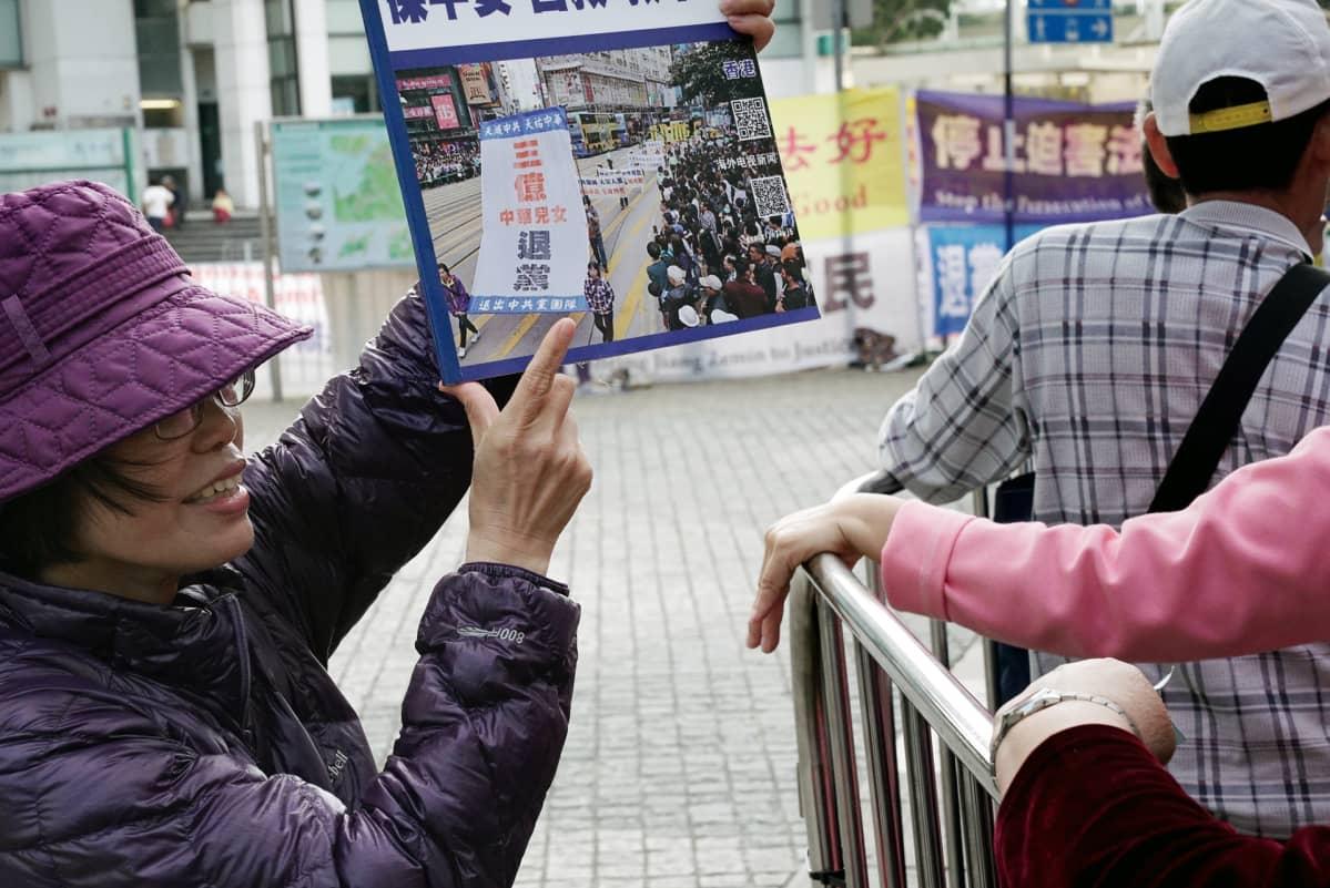 Liao Limei kehottaa turisteja eroamaan Kiinan kommunistisesta puolueesta.
