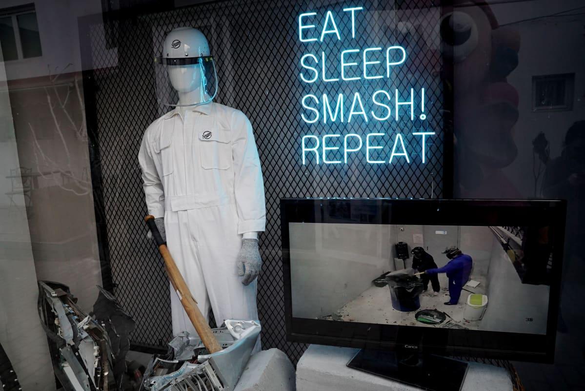 Eat sleep smash repeat -loisteputkikyltti seinällä, vieressä valkoiseen haalariin puettu mallinukke.