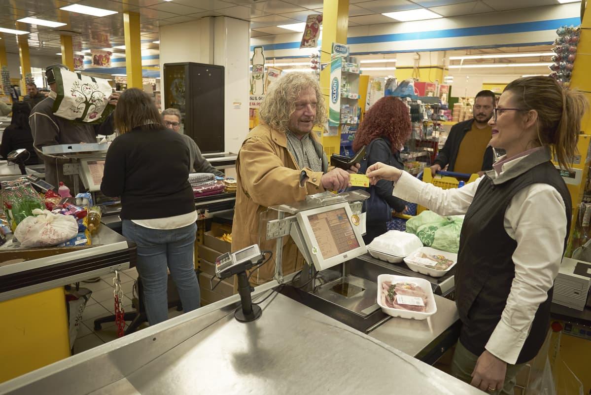 Filipponi ojentaa keltaista korttia myyjälle kaupan kassalla. Kassalla on elintarvikkeita.