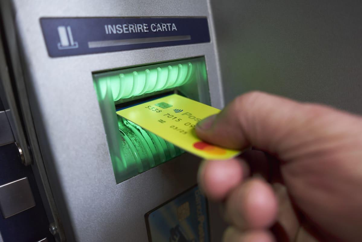 Käsi työntää keltaista muovikorttia pankkiautomaatin kortinlukijaan.