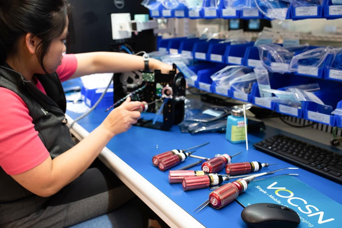 Nainen valmistaa hengityskoneen osia.