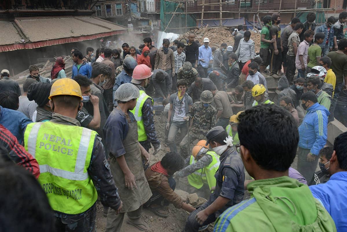 Ihmiset raivaavat pahasti vaurioutunutta UNESCON maailmanperintökohteeksi nimettyä Durbarin toria Kathmandussa 25. huhtikuuta.