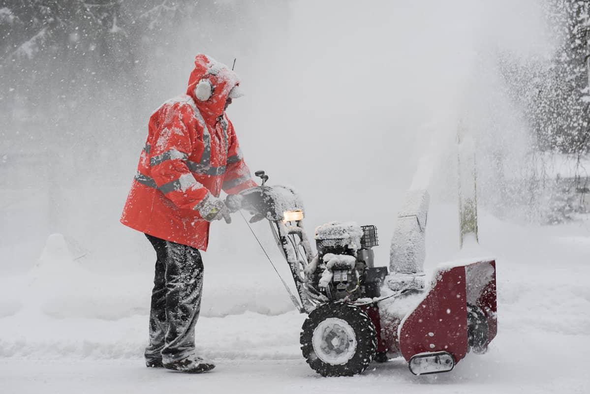 Mies työntää lumilinkoa.