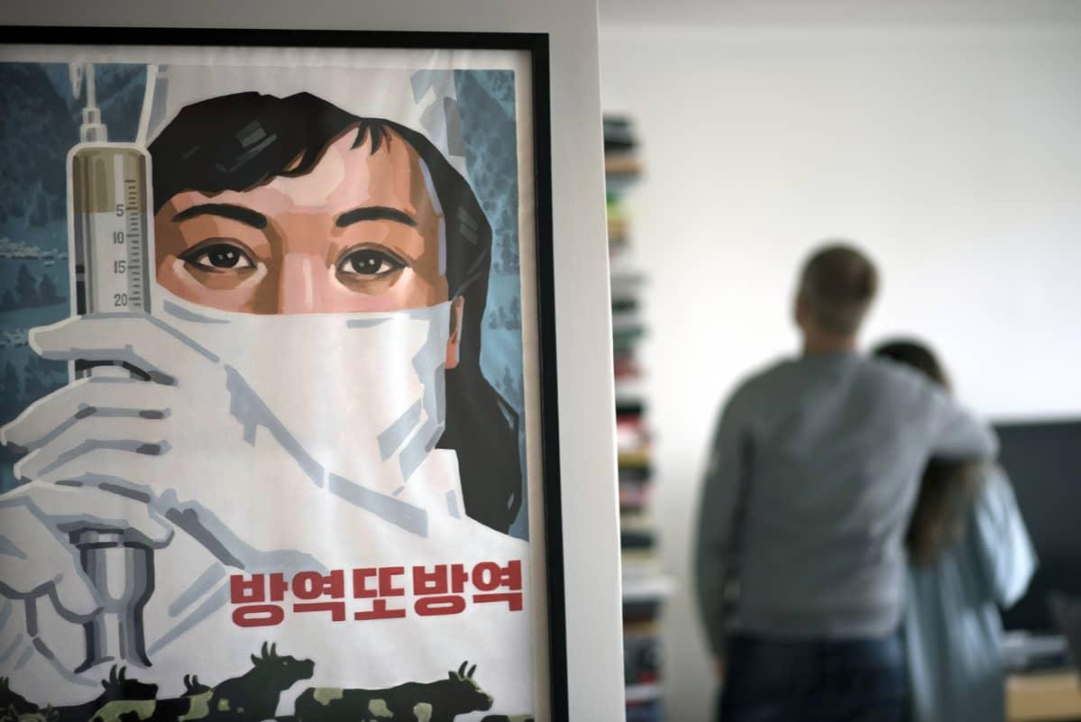 Pohjoiskorealainen propagandajuliste seinällä.