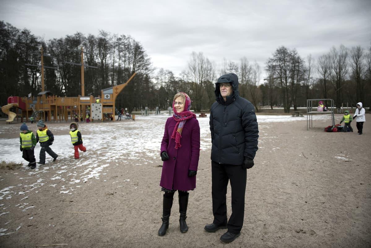 Pariskunta seisoo leikkipuiston edustalla.