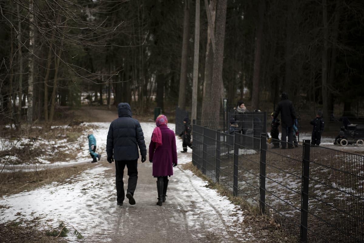 Pariskunta kävelee leikkipuiston ohitse.