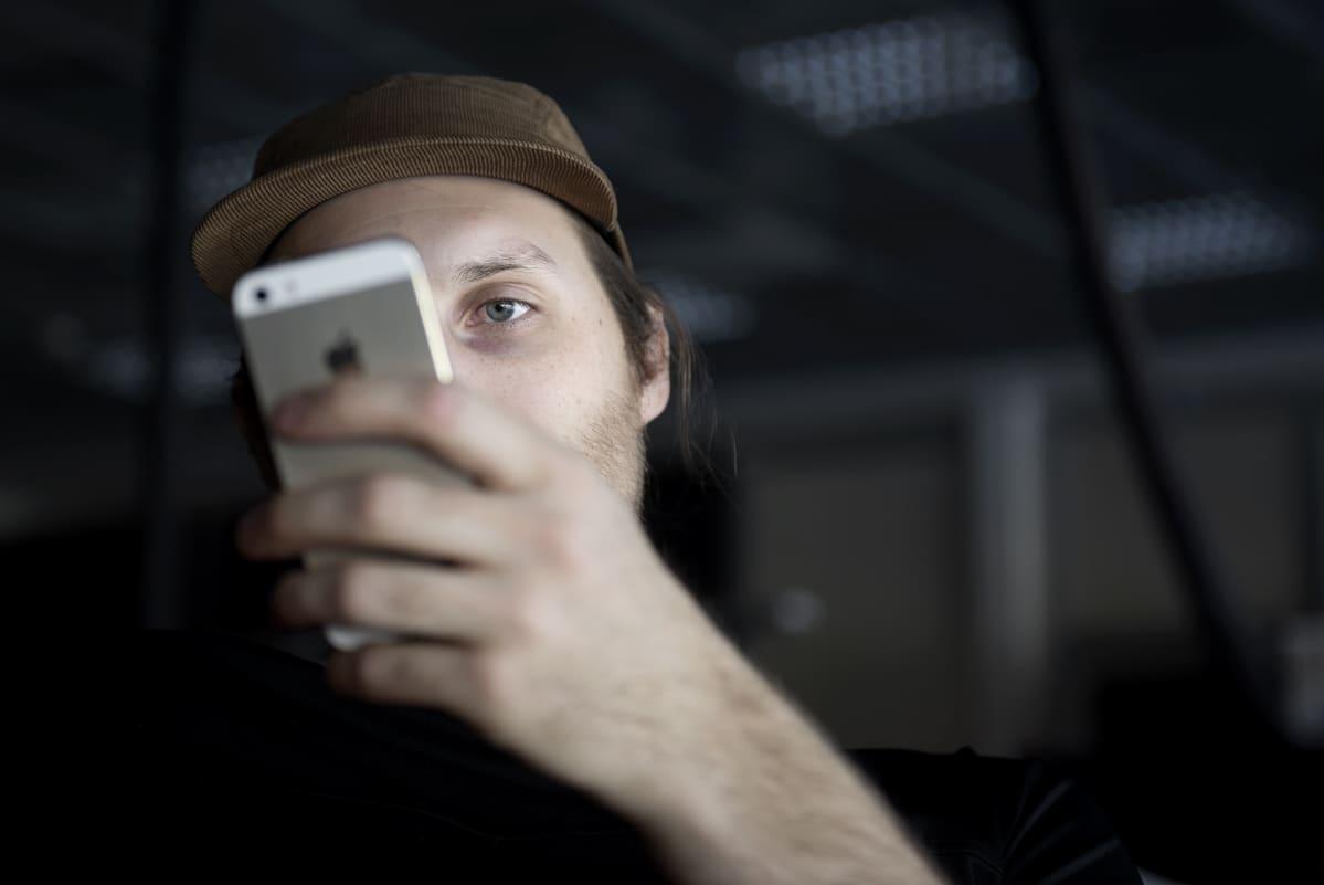 Mies tutkii älypuhelintansa.
