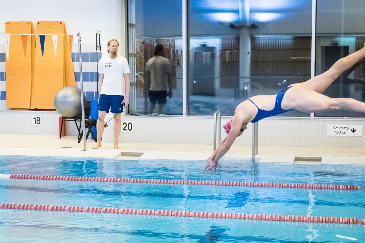 Valmentaja Toni Piirainen seuraa kun Jenna Laukkanen hyppää altaaseen.