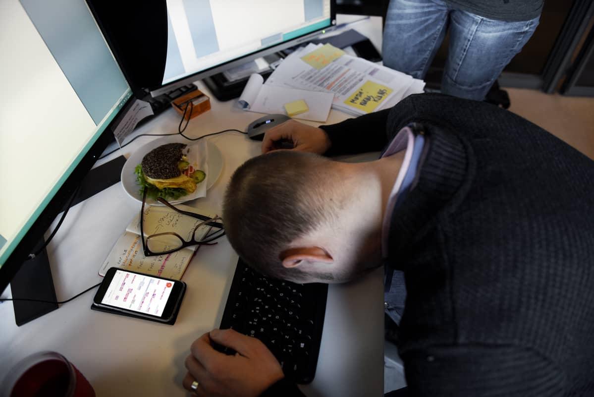 Työntekijä nukkuu työpöytänsä ääressä.