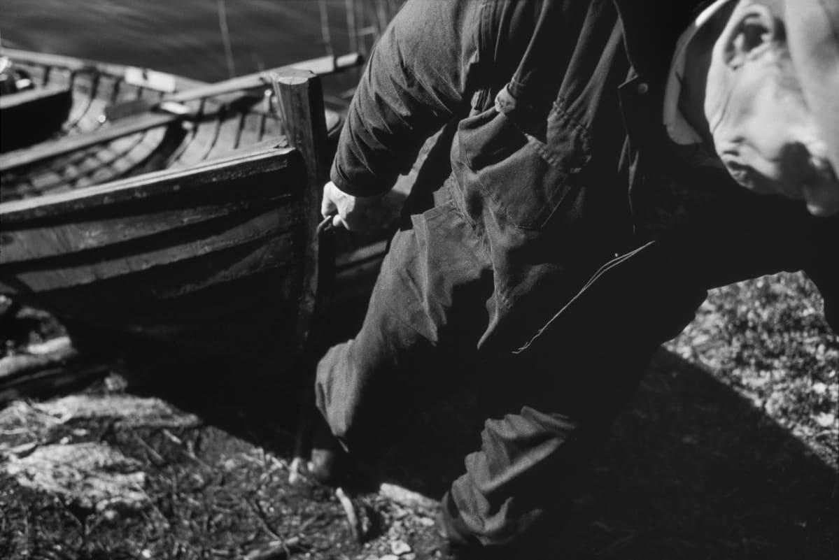 Isä vetää venettä maalle