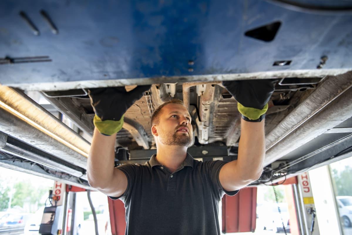 Autokatsastaja Tommi Pasanen tarkastaa katsastettavaksi tulleen auton pohjaa
