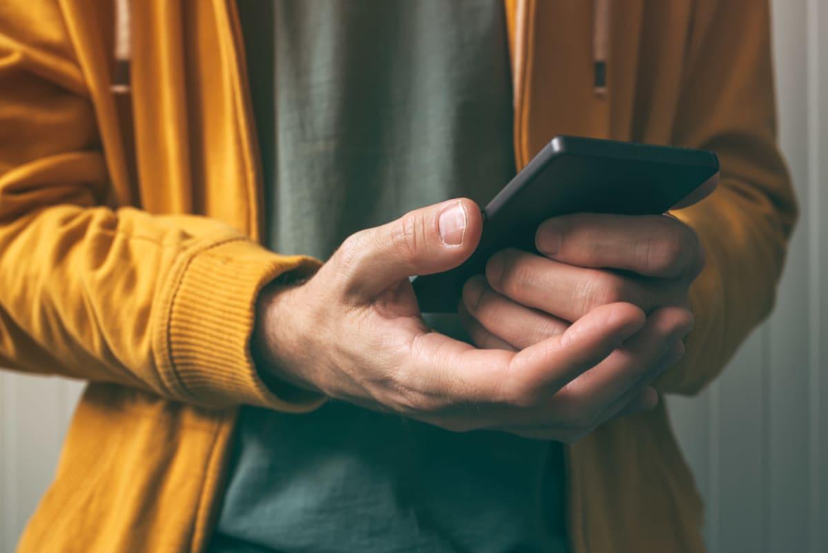 En person med gul munkjacka håller i en svart telefon.