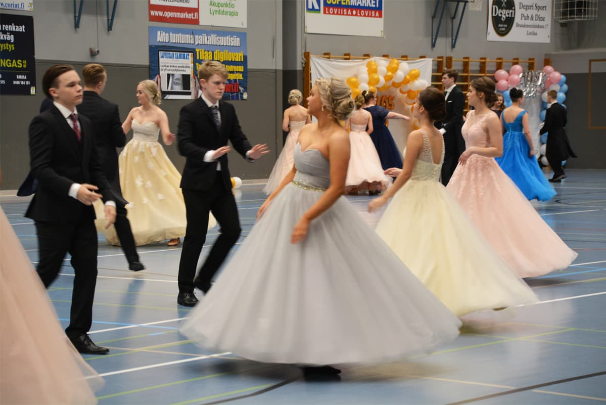 Ungdomar i festkläder dansar omkring i en gympasal.