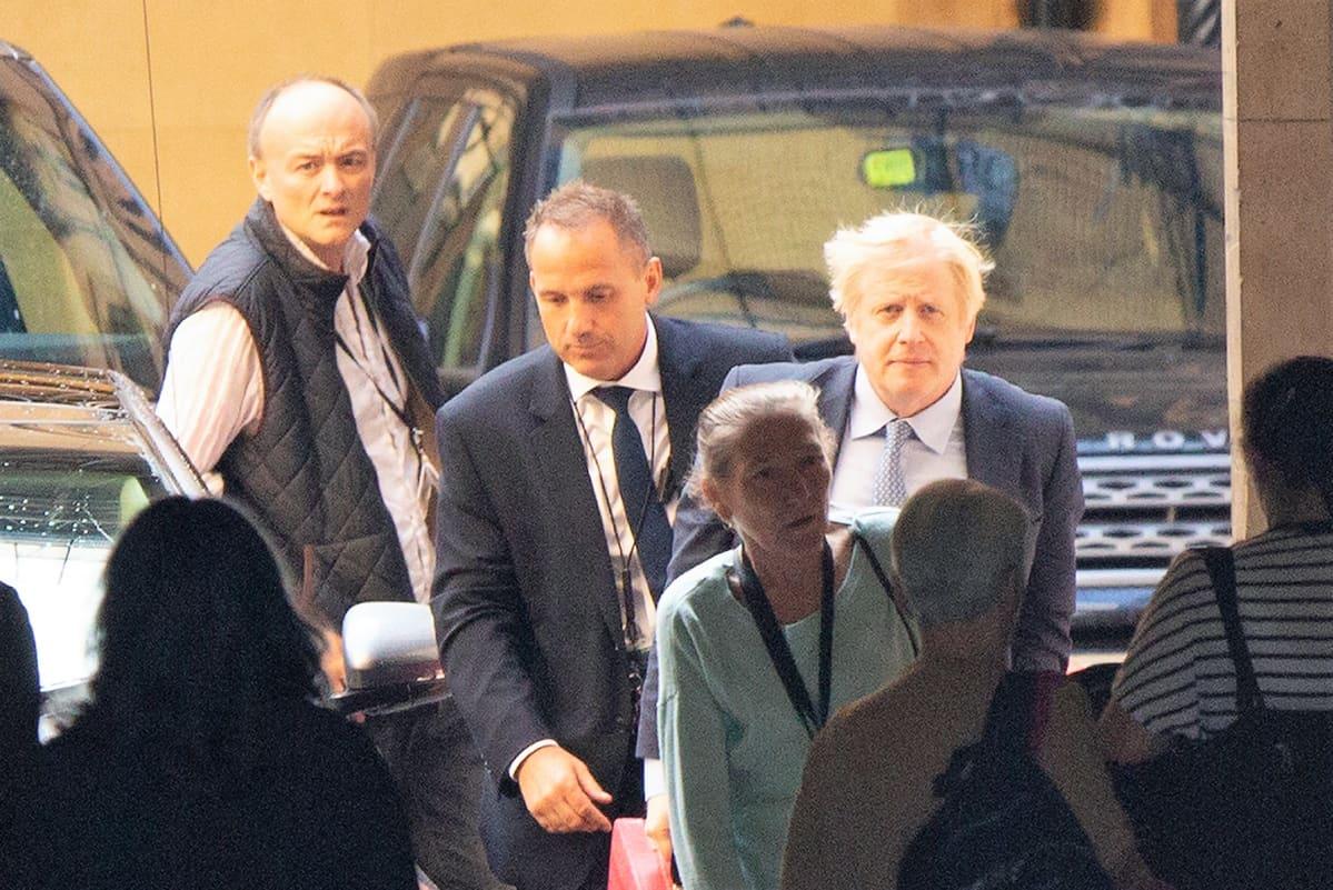 Dominic Cummings ja Boris Johnson saapuvat parlamenttiin pääministerin kyselytunnille. Johnsonilla on tumma puku, Cummingsilla liivit ja valkoinen paita.