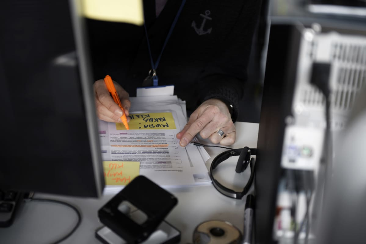 Työntekijä alleviivaa tekstiä toimistossa.