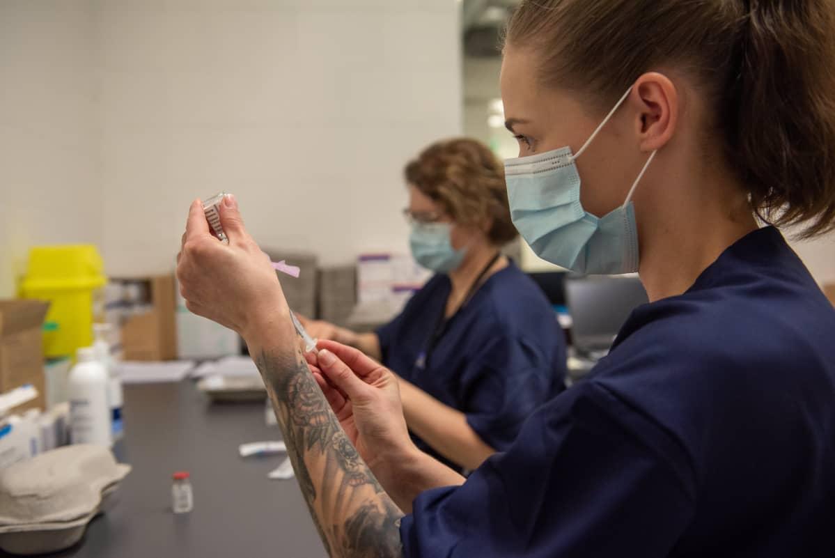 Astra Zeneca -rokotetta valmistava sairaanhoitajat Porvoon rokotuskeskuksessa. 18.3.2021.