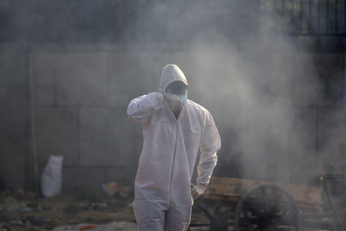 Suojapukuun pukeutunut omainen polttohautauspaikalla New Delhissä