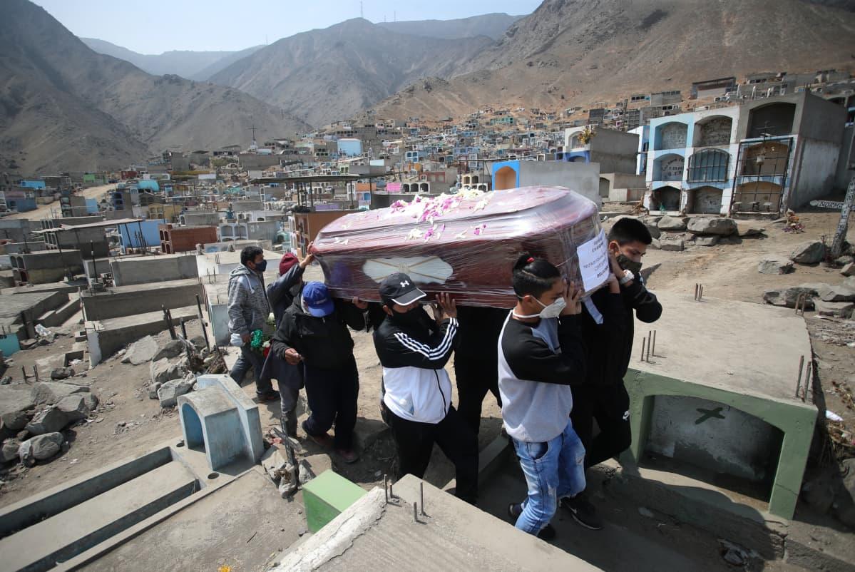 Miehet kantavat ruumisarkkua haudettavaksi perulaisella hautausmaalla.