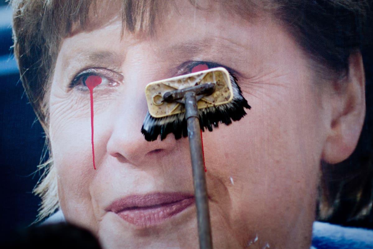 Merkel-mainosposteria puhdistetaan.