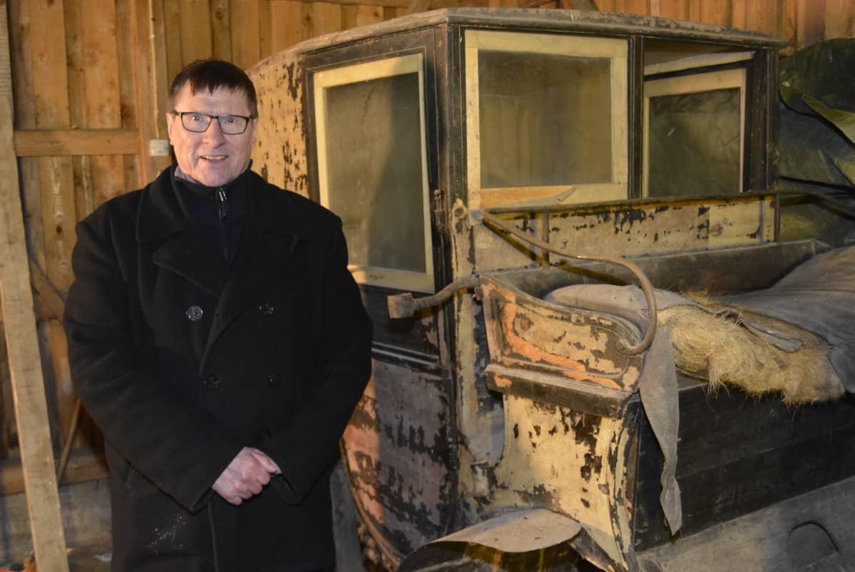 Vanhat hevosvaunut rapistuvat Kyminlinnan entisen varuskunnan varastossa. Vaunujen vieressä tietokirjailija Risto Valkeapää.
