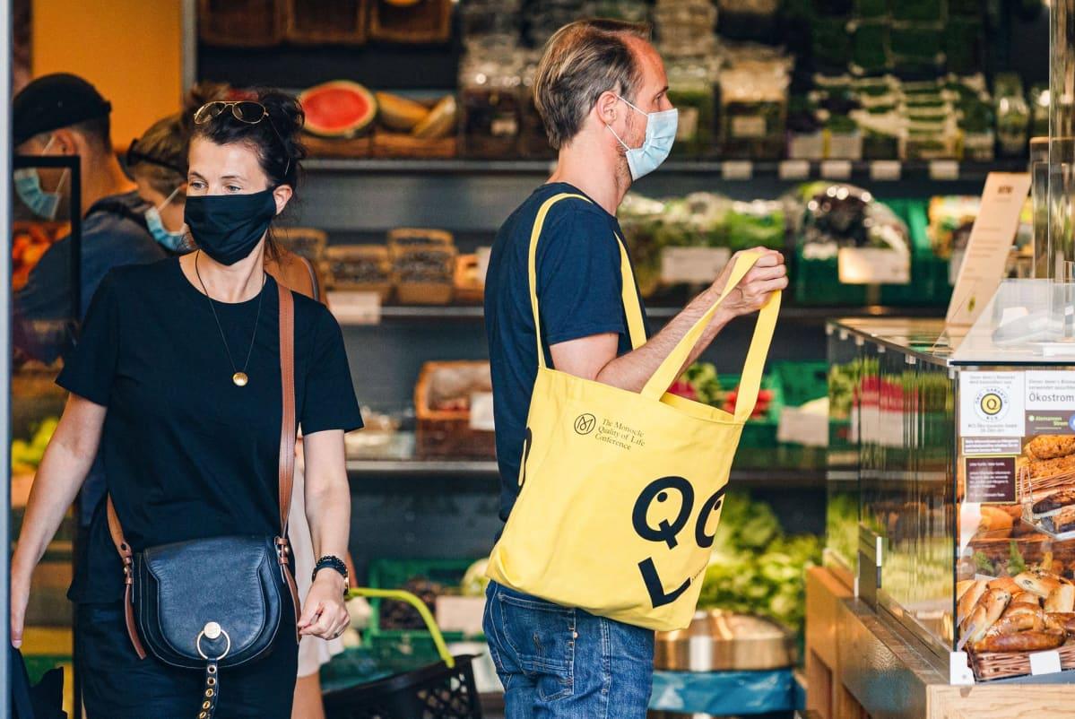 Ihmisiä kaupassa maskit kasvoilla