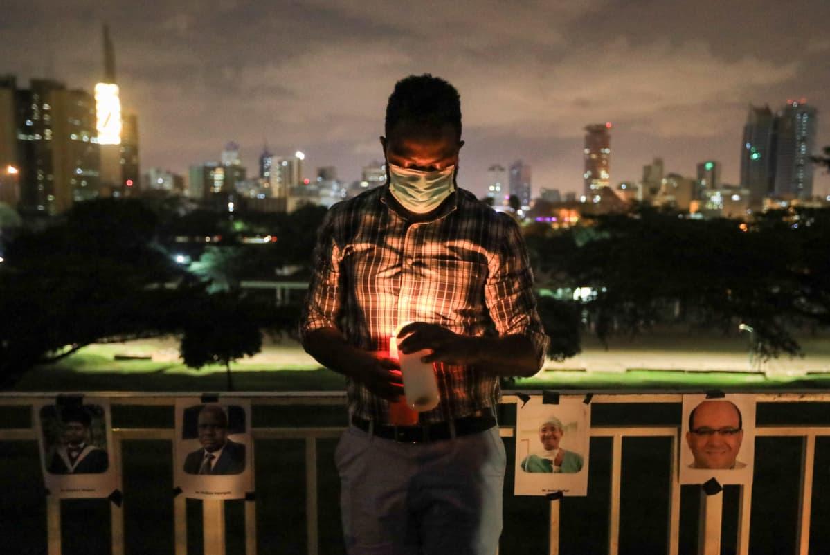 Kenialainen lääkäri sytyttyi kynttilän koronapandemian aikana menehtyneen kollegansa muistoksi Nairobissa 9. joulukuuta 2020.