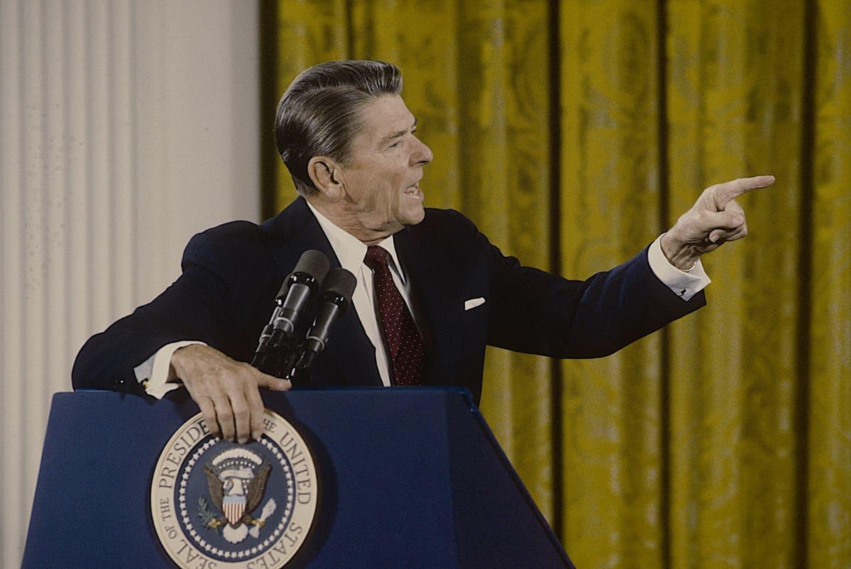 Presidentti Ronald Reagan puhujapöntössä viittoilee voimakkaasti.