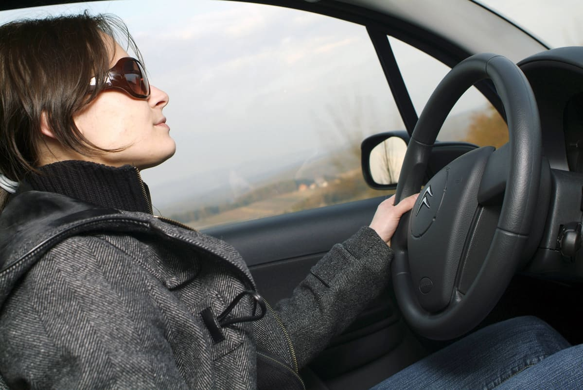 Aurinkolaseja käyttävä kuljettaja.