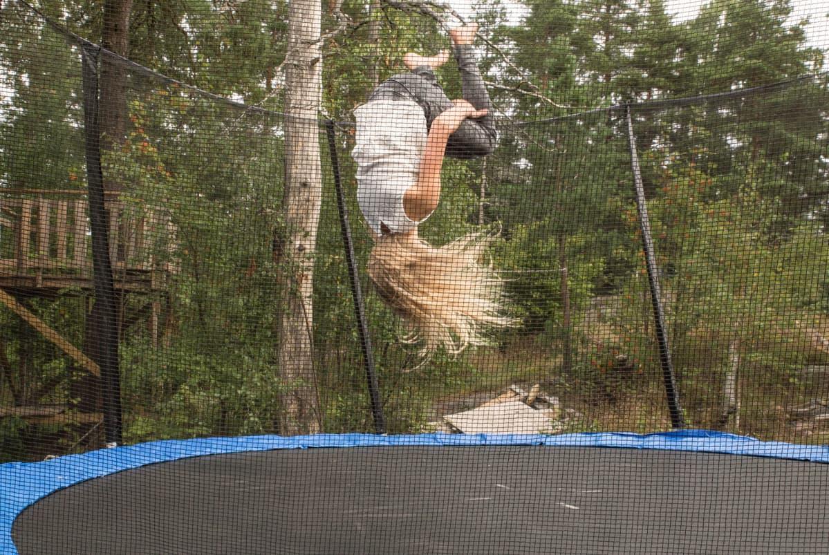 Tyttö hyppää voltin trampoliinilla.