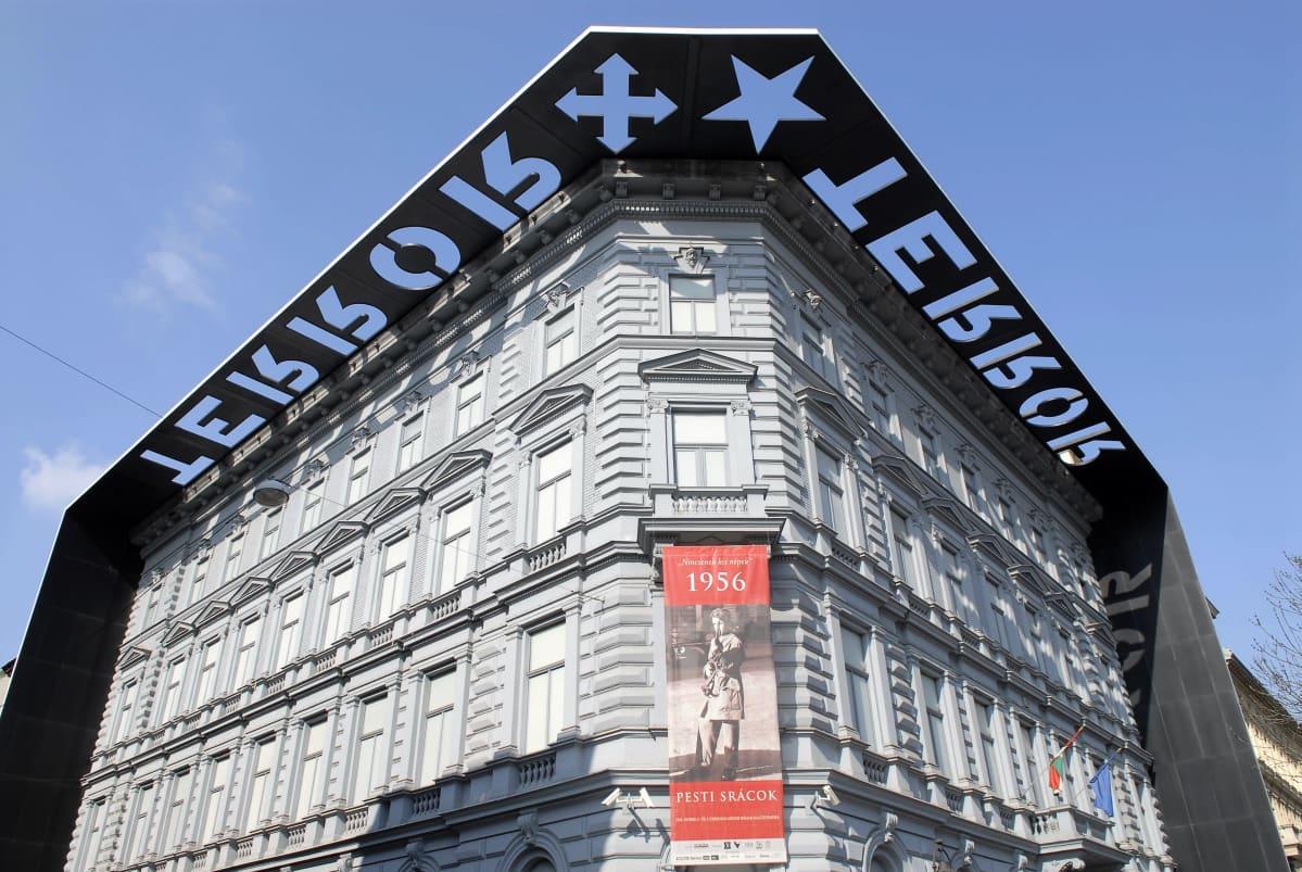 Kuva esittää Terrorin talon julkisivua. Katonrajassa kulkevat mustat palkit, joissa lukee TERROR. Talon seinällä on juliste, jossa mainostetaan vuoden 1956 kansannousua käsittelevää näyttelyä.