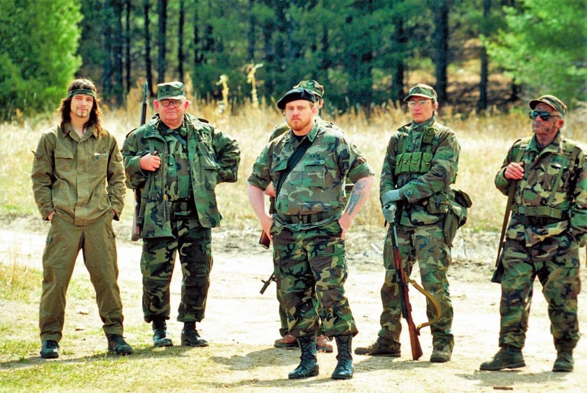 Joukko miehiä erilaisissa vihreissä maastoasuissa seisoo aukiolla aseiden kanssa.