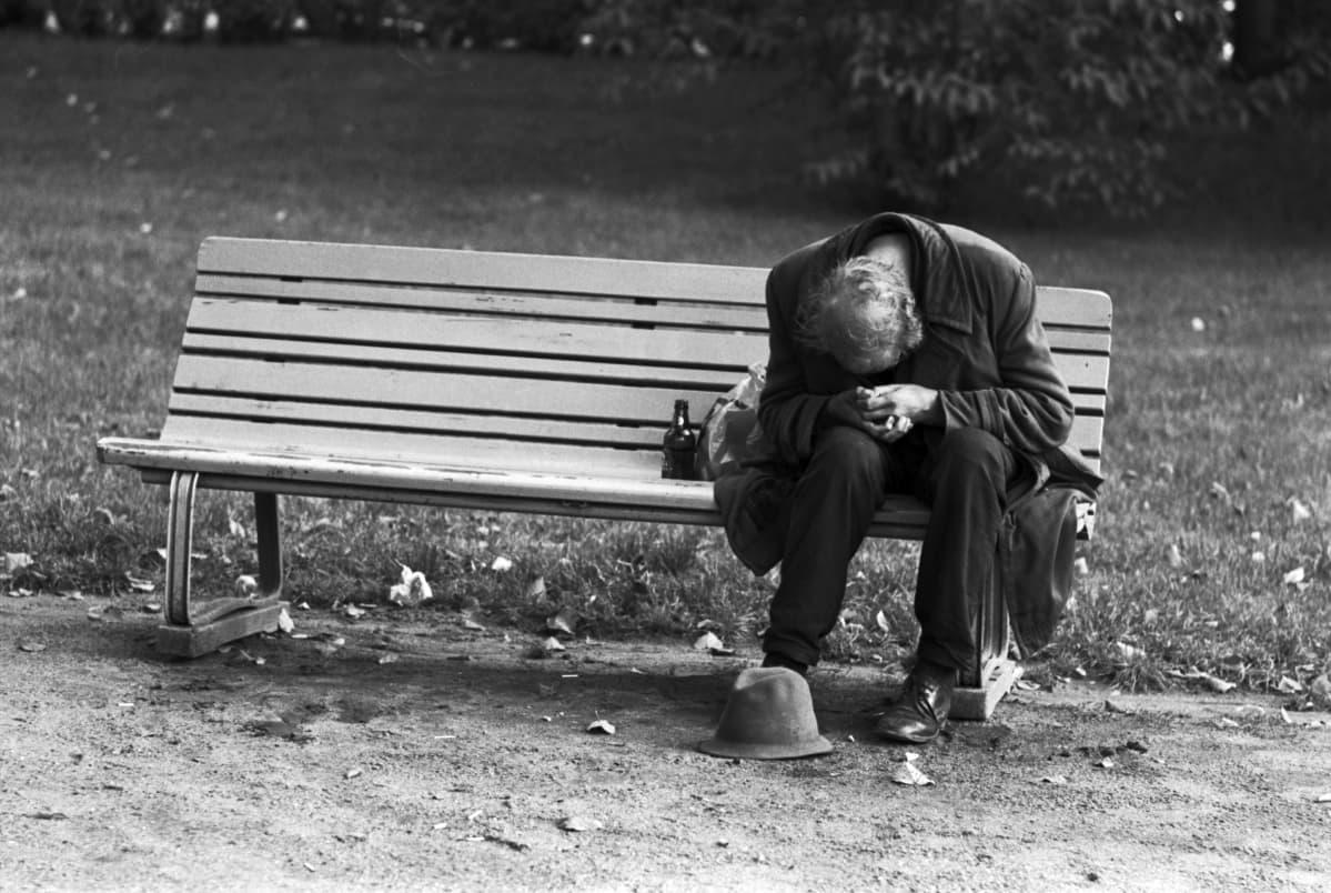 Väsynyt puistojen mies istumassa pää riipuksissa penkillä Varsapuistikossa.