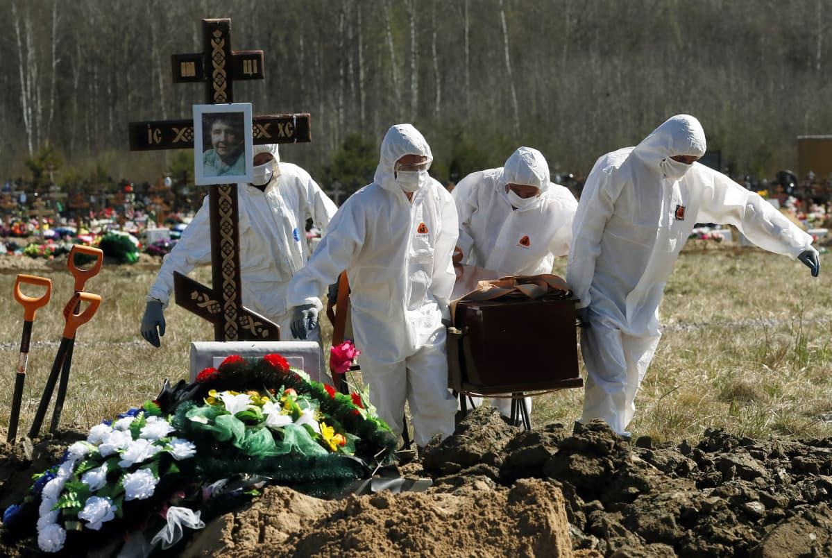 Suojavarusteisiin pukeutuneet työntekijät kantavat arkkua hautausmaalla Pietarissa.