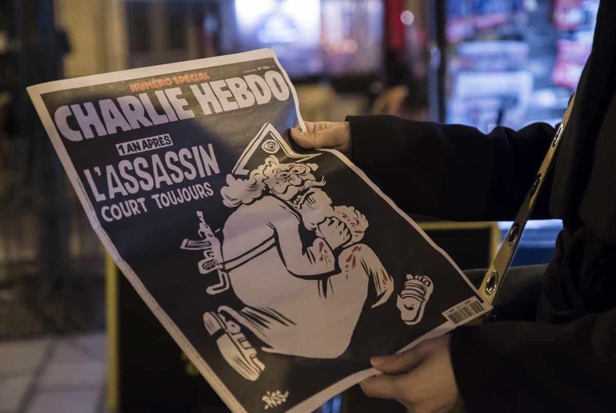 Charlie Hebdo-lehden erikoisnumerossa muistetaan vuoden takaista terrori-iskua. Lehden etukannessa parrakas jumala, jonka selässä rynnäkkökivääri.