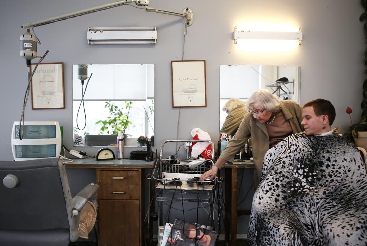 Nainen leikkaa miehen hiuksia.