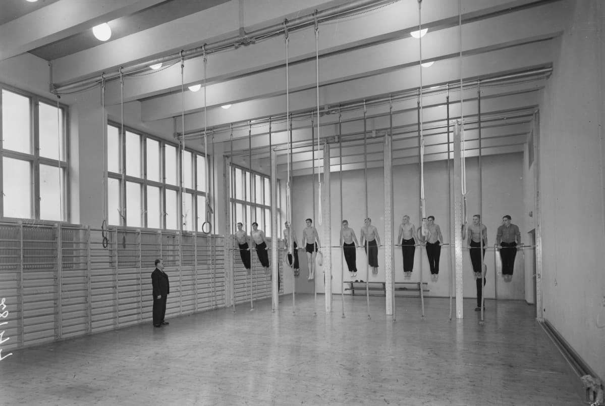 Kymmenen nuorta miesti voistelee koulun salissa renkailla.