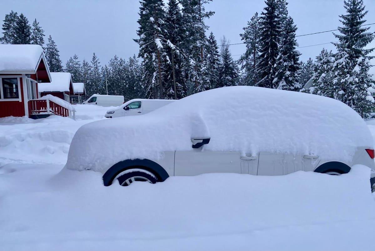 Lumeen peittynyt auto omakotitalon pihassa