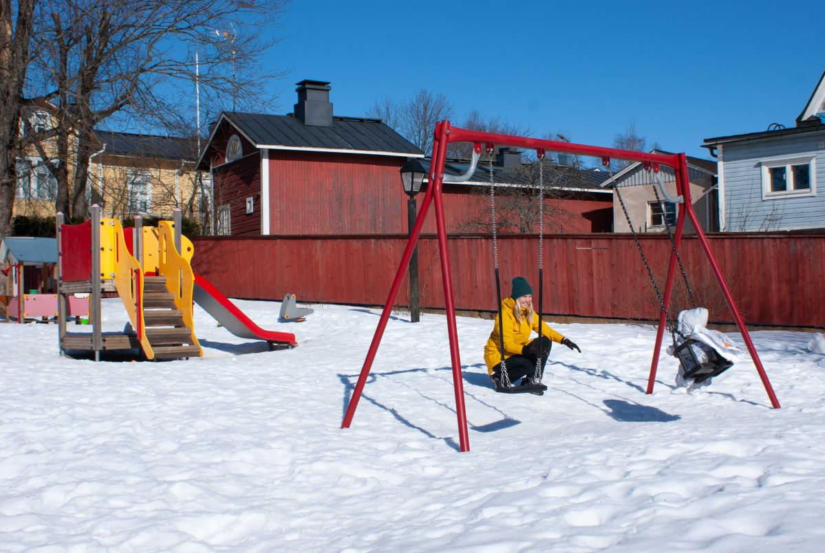 Emma keinuttaa lastaan puiston keinussa.