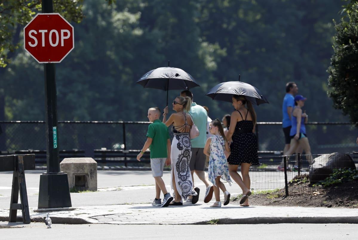 Kävelijöillä oli omat varjot mukana New Yorkin keskuspuistossa 20. heinäkuuta.