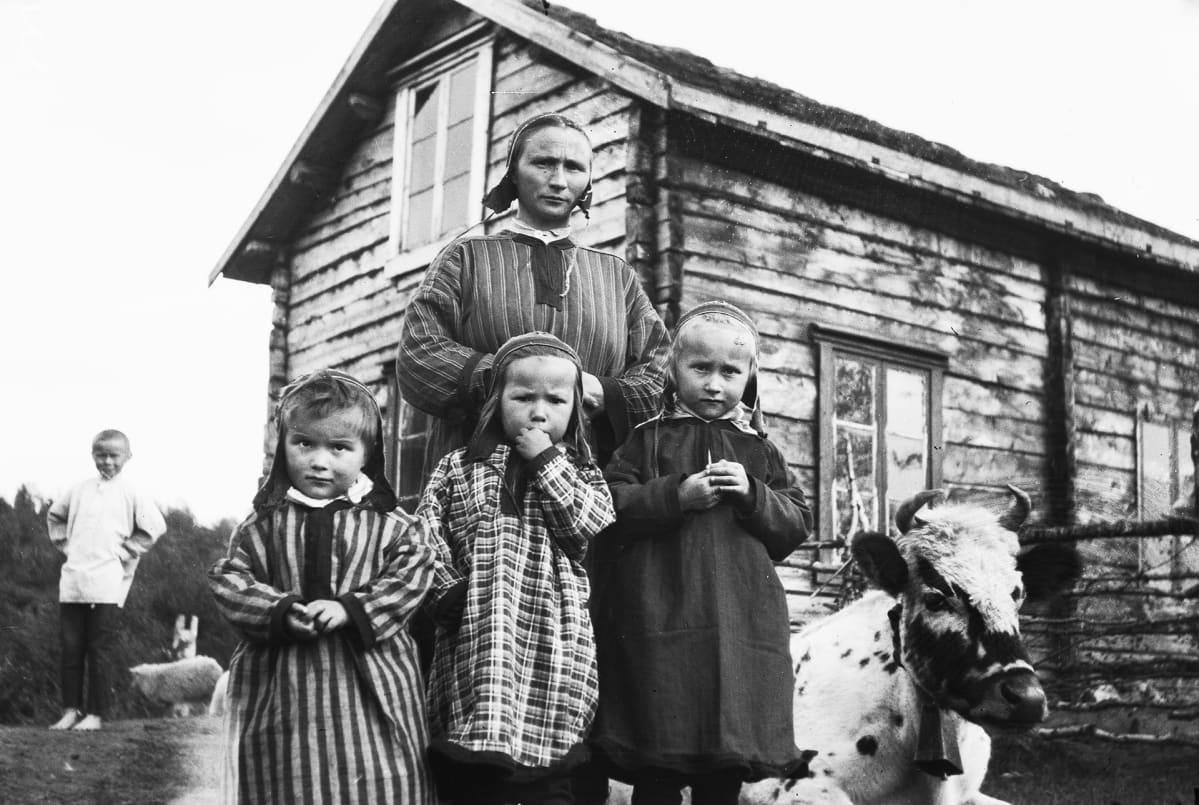 Inarilaisia pikkutyttöja ja heidän äitinsä kodin pihalla.