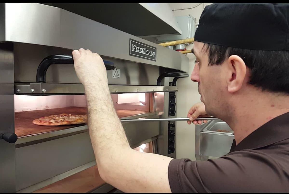 Basri Gashi paistaa pizzaa.