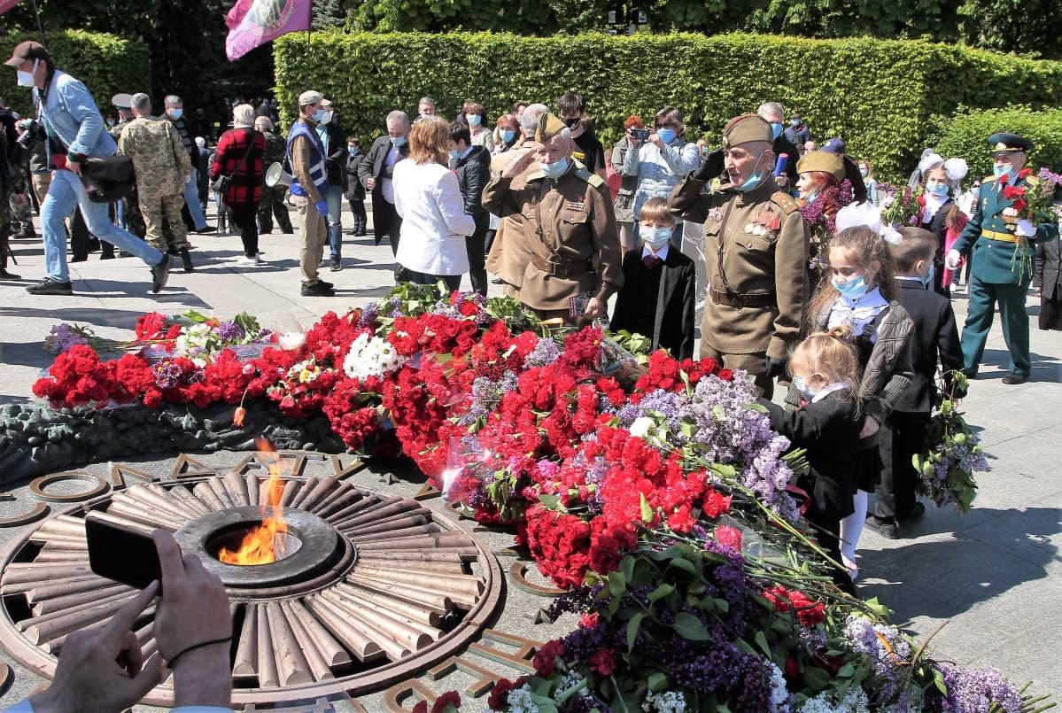 Toisen maailmansodan univormuihin pukeutuneet vanhat miehet tekevät lasten kanssa kunniaa ikuisen tulen äärellä. Muistomerkin juurella on suuri määrä punaisia kukkia.