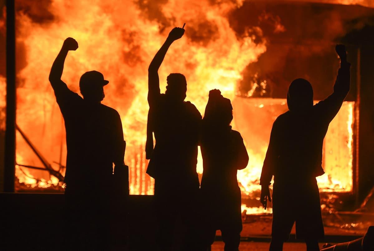 Mellakoitsijat seisovat palamaan sytytetyn kaupan edustalla Minneapolisissa 29. toukokuuta 2020.