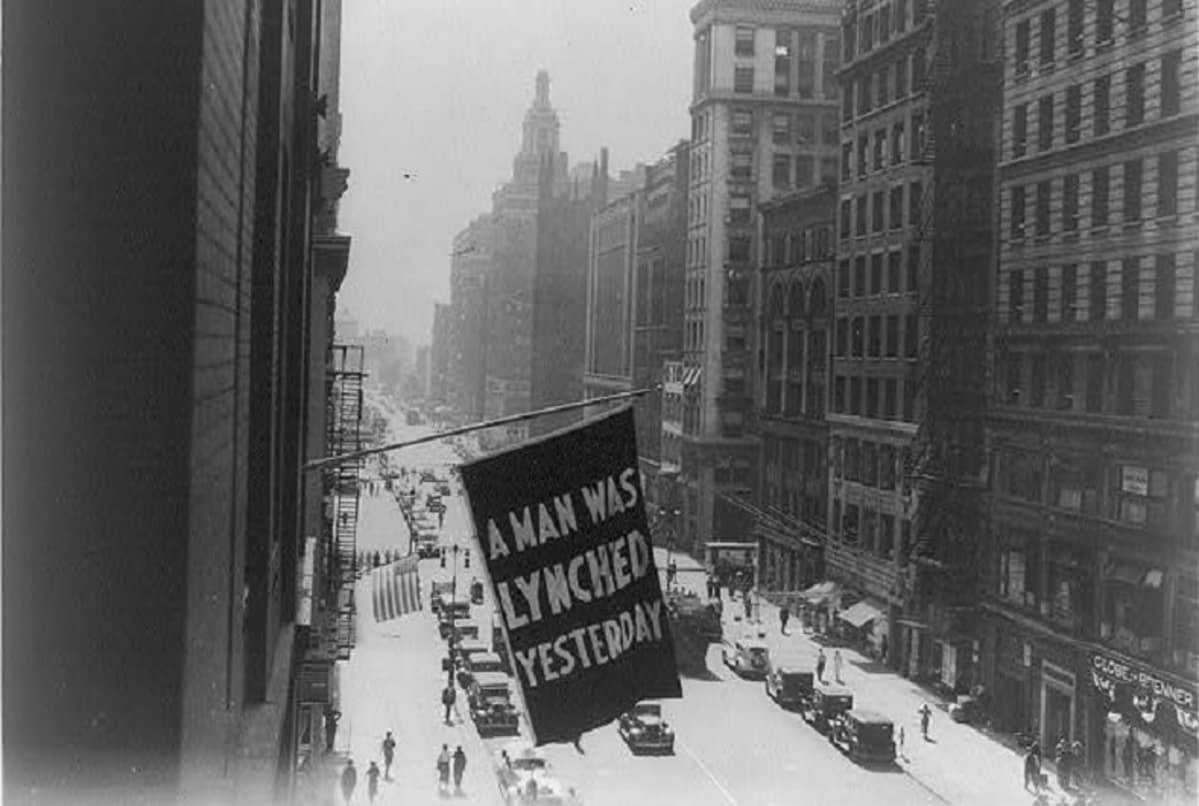 """Mustavalkoinen kuva kadusta autoineen ja ihmisineen. Ikkunasta liehuu lippu, jossa lukee """"A man was lynched yestarday""""."""