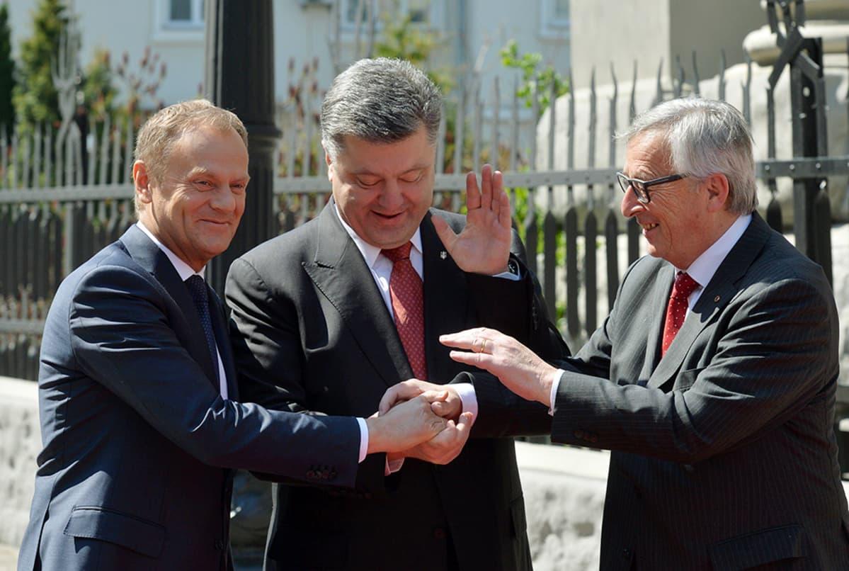 Ukrainan presidentti Petro Porošenko (kuvassa keskellä) kätteli Euroopan komission puheenjohtajan Jean-Claude Junckerin (oik.) ja Eurooppa-neuvoston puheenjohtajan Donald Tuskin (vas.) kanssa Kiovassa 27. huhtikuuta.