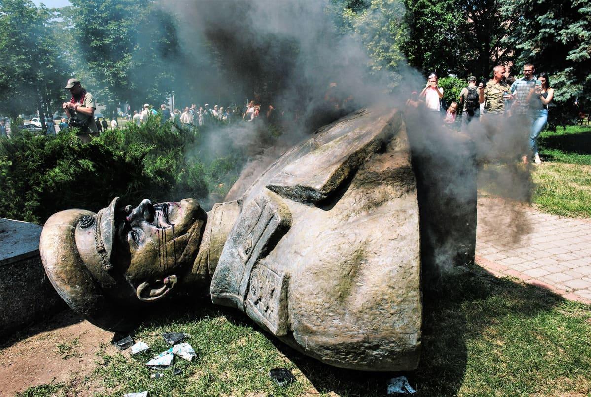 Marsalkka Zhukovin patsas on kaadettuna maassa. Taustalla näkyy mielenosoittajia. Jokin savuaa.