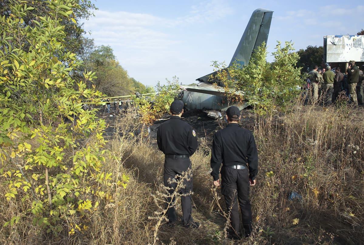 Kaksi miestä katsoo maahan pudonnutta lentokonetta.