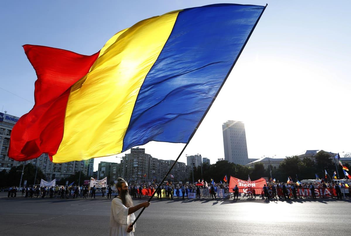 Mielenosoitukset jatkuvat Romaniassa. Ihmiset kantavat Romanian lippuja ja tekstilakanoita.